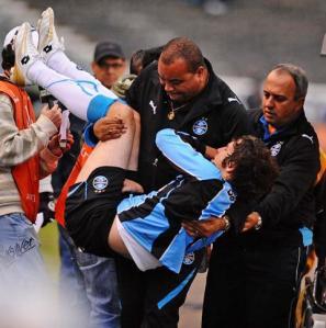 Mário Fernandes, lesionado, sai carregado pelo segurança do Grêmio - Foto: Valdir Friolin (ClicRBS)